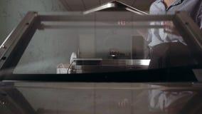 Una donna del confettiere elimina i pacchetti al forno per il dessert dal forno, tortini Cucina moderna, classe matrice culinaria archivi video