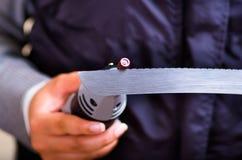 Una donna del hardworker che per mezzo di un lucidatore sopra un pezzo grigio del coltello su un fondo di legno Fotografia Stock