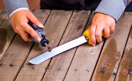 Una donna del hardworker che per mezzo di un lucidatore sopra un pezzo grigio del coltello su un fondo di legno Fotografie Stock
