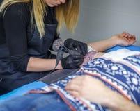Una donna dell'artista del tatuaggio disegna con la sua macchina del tatuaggio, un tatuaggio sopra fotografie stock
