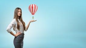 Una donna di affari bionda sta e tiene una palma della mano su con il piccolo aerostato rosso e bianco caldo sopra  Fotografia Stock