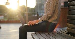 Una donna di affari in una camicia sta lavorando al suo computer portatile sul banco Giorno soleggiato, via sui precedenti archivi video