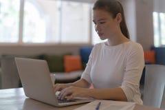 Una donna di affari che lavora al suo computer nell'ufficio fotografie stock