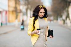 Una donna di affari che parla tramite telefono cellulare e che tiene una tazza di caffè Giovane ragazza alla moda esile in vestit Fotografia Stock