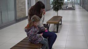 Una donna di affari controlla le sue annotazioni in un centro commerciale, figlia sta aspettando la madre video d archivio
