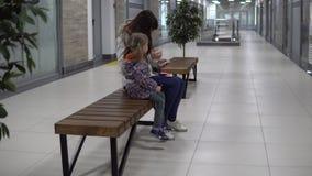 Una donna di affari controlla le sue annotazioni in un ufficio, figlia sta aspettando la madre stock footage