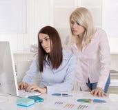 Una donna di affari di due giovani che esamina deludente lo schermo in Th Immagini Stock Libere da Diritti