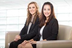 Una donna di affari di due giovani che si siede accanto a ogni altro Immagine Stock