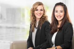 Una donna di affari di due giovani che si siede accanto a ogni altro, sorriso Fotografia Stock