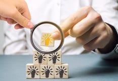 Una donna di affari mette i blocchi di legno con una lampadina di un'idea Innovazione e nuove soluzioni fresche Ispirazione dell' immagini stock