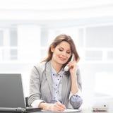 Una donna di affari in vestiti convenzionali sul telefono Fotografia Stock