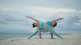 Una donna di due asiatici che gioca posa di yoga sulla spiaggia del mare archivi video