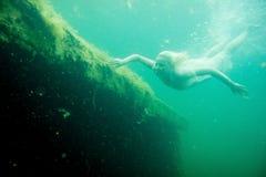 Una donna di galleggiamento Ritratto subacqueo Ragazza nel nuoto bianco del vestito nel lago Piante marine verdi, acqua immagine stock libera da diritti