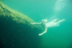 Una donna di galleggiamento Ritratto subacqueo Ragazza nel nuoto bianco del vestito nel lago Piante marine verdi, acqua fotografia stock