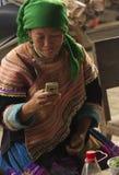 Una donna di Hmong del fiore sta mandando un sms a a Bac Ha Fotografia Stock