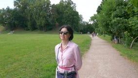 Una donna di mezza età in occhiali da sole cammina lentamente nel parco stock footage