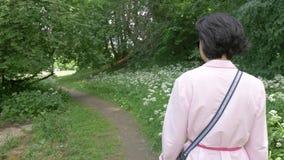 Una donna di mezza età in occhiali da sole cammina lentamente nel parco archivi video