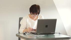 Una donna di mezza età riordina i suoi conti Home banking, attività bancarie online stock footage