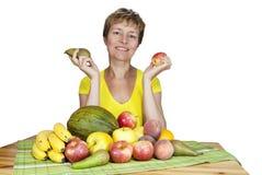 Una donna di mezza età sorridente con frutta. Fotografia Stock