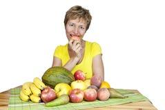 Una donna di mezza età sorridente con frutta. Immagine Stock Libera da Diritti