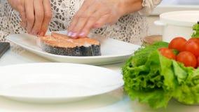 Una donna di sessanta pesci rossi della bistecca dei sali e mette un pezzo di trota in una doppia caldaia stock footage