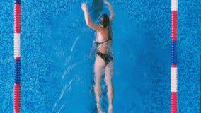 Una donna dimostra uno stile di nuoto di movimento strisciante di prefetto stock footage