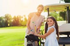 Una donna e una ragazza ottengono i club di golf dalla borsa Ragazza che esamina la macchina fotografica Fotografia Stock Libera da Diritti