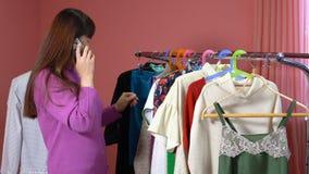 Una donna esamina i vestiti in uno studio dell'abbigliamento archivi video