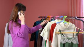 Una donna esamina i vestiti in uno studio dell'abbigliamento video d archivio