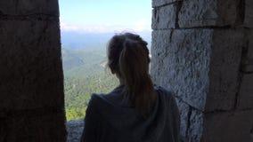Una donna esamina le montagne attraverso una finestra sulla torre di osservazione immagine stock libera da diritti
