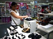 Una donna esamina un paio delle scarpe nel dipartimento della scarpa del centro commerciale della città di MP nella città di Tayt immagine stock libera da diritti