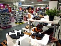 Una donna esamina un paio delle scarpe nel dipartimento della scarpa del centro commerciale della città di MP nella città di Tayt fotografia stock