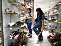 Una donna esamina un paio delle scarpe nel dipartimento della scarpa del centro commerciale della città di MP nella città di Tayt fotografie stock