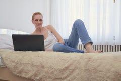 una donna, esaminando macchina fotografica, stenditura di rilassamento a letto stanza spaziosa bianca, finestre di luce del giorn Immagine Stock