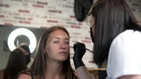 Una donna fa le belle sopracciglia spesse in un salone di bellezza stock footage