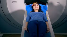 Una donna fa scorrere fuori da un anello aperto di un CT-analizzatore archivi video
