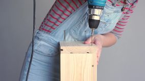 Una donna fa un lavoro non femminile - perfora un pozzo con un cacciavite in una scatola di legno archivi video