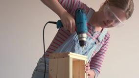 Una donna fa un lavoro non femminile - perfora un pozzo con un cacciavite in una scatola di legno stock footage