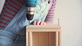Una donna fa un lavoro non femminile - perfora un pozzo con un cacciavite in una scatola di legno, movimento lento stock footage