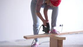 Una donna fa un lavoro non femminile - segare un bordo di legno con un puzzle elettrico stock footage