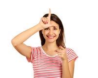 Una donna felice dà un segno del perdente sulla sua fronte, esaminante vi ed indicante il suo dito alla macchina fotografica isol Immagini Stock