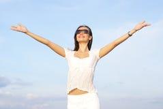 Una donna felice in vetri ed in un vestito bianco Immagini Stock