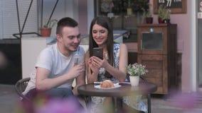 Una donna in foto di sorveglianza di un uomo su uno smartphone un caffè di estate stock footage