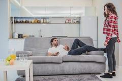 Una donna frustrata che parla con suo marito mentre guardando una TV Un uomo che si siede sullo strato mostra un gesto con il suo fotografia stock