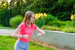 Una donna funziona nel parco e controlla i suoi puls fotografia stock libera da diritti