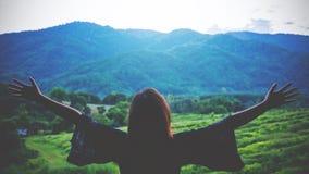 Una donna gira indietro stare e l'allungamento delle armi con la natura e la montagna Fotografia Stock Libera da Diritti