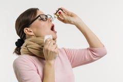 Una donna gocciola le gocce per il naso Priorità bassa bianca Immagine Stock Libera da Diritti
