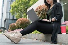 Una donna graziosa dello studente sta utilizzando il computer portatile Immagine Stock