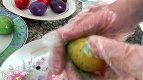Una donna in guanti dipinge le uova video d archivio