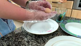 Una donna in guanti dipinge le uova archivi video